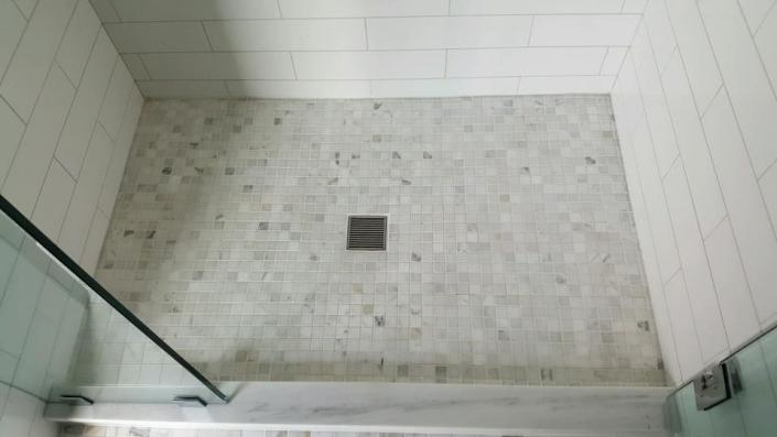 We've added depth and a unique flair to this bathroom shower with this multi-colored tile flooring.