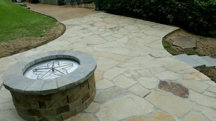 Complete with a gorgeous fire pit, this natural stone patio is absolutely breathtaking!
